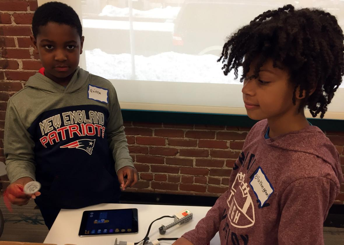 Quintyn Scott (left) and Ella Bartholomew program robots at a recent CoderDojo session in Boston.