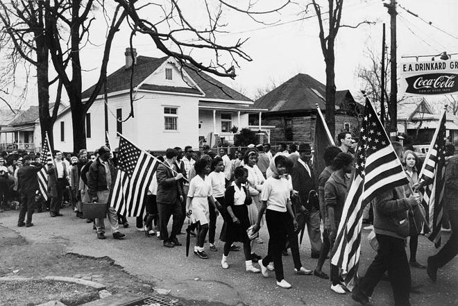 Participants, some carrying American flags, march from Selma to Montgomery, Alabama, in 1965