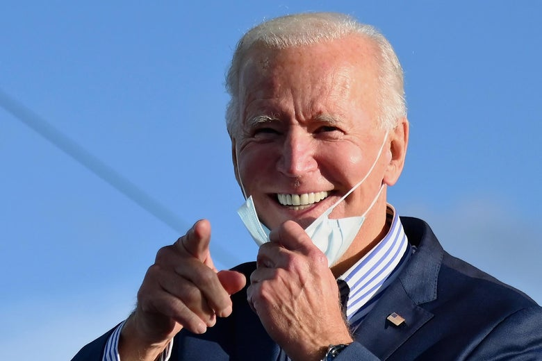 Biden grins, pulling his mask down with one hand as he points toward the camera with the other hand