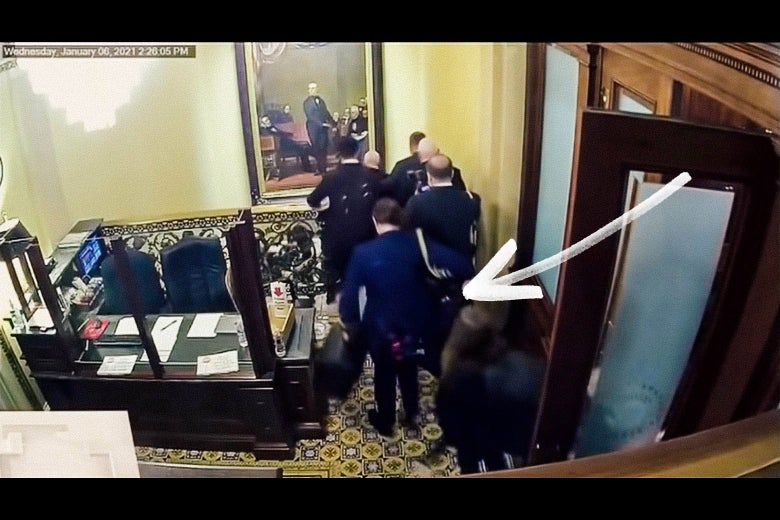 Video still showing an Air Force security officer carrying the nuclear satchel behind Pence, with an arrow pointing at the satchel