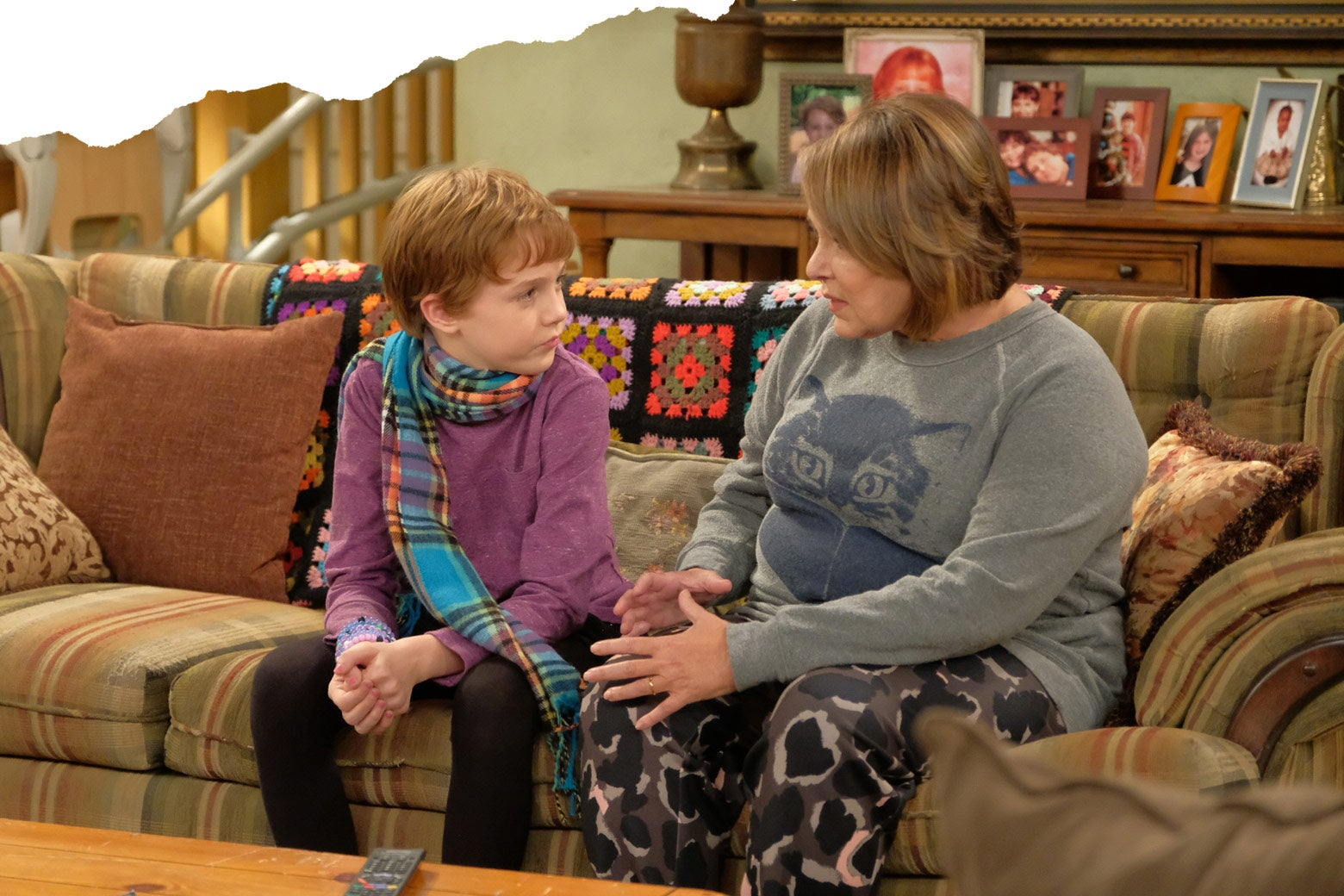 Mark and Roseanne sit on the couch in a scene from the TV show Roseanne.