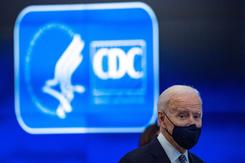 Joe Biden, wearing a face mask, stands in front of a sign with the CDC logo.