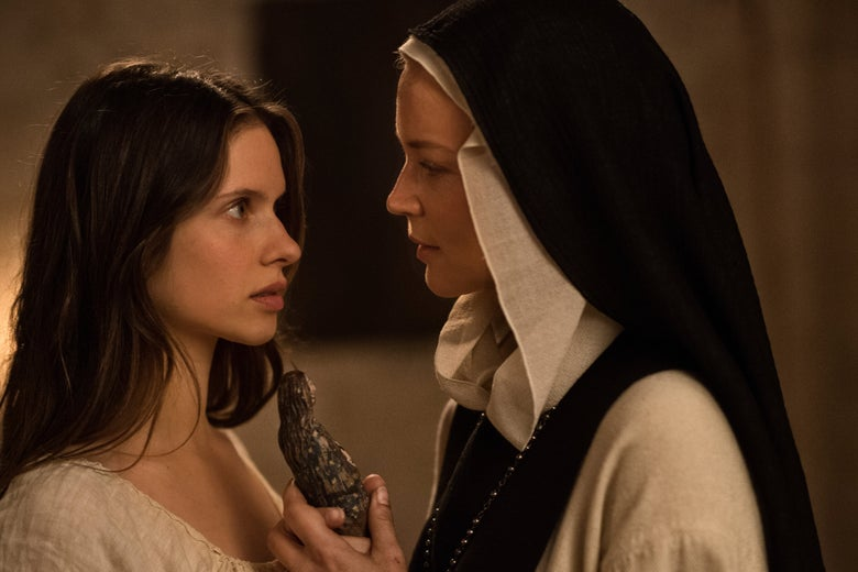 Daphne Patakia looking at Virginie Efira, who holds a wooden Virgin Mary statue, in a still from Paul Verhoeven's movie Benedetta.