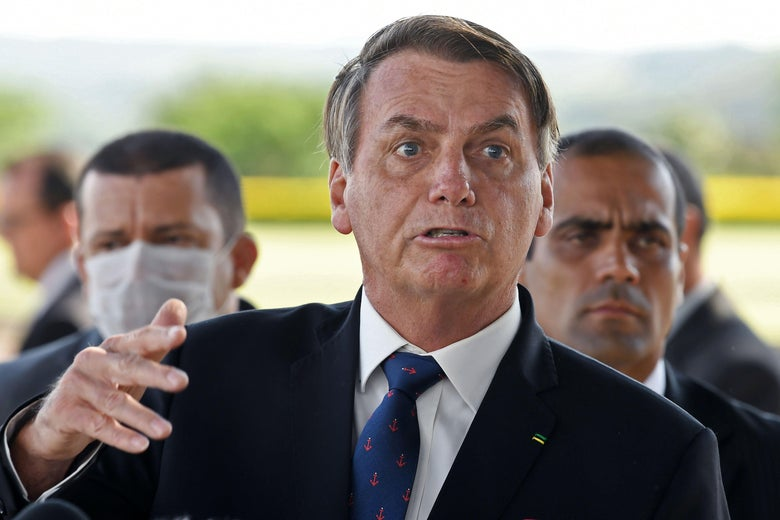 Bolsonaro speaks. An aide behind him wears a surgical mask.