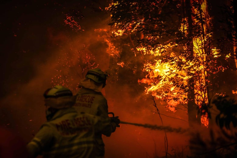 A pair of firefighters spray water from a hose on a huge orange blaze that is swallowing trees.