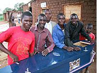 Macdonald (second from left), Julius Chinangwa (far right), some of their workmen, and the $600 blue formica model