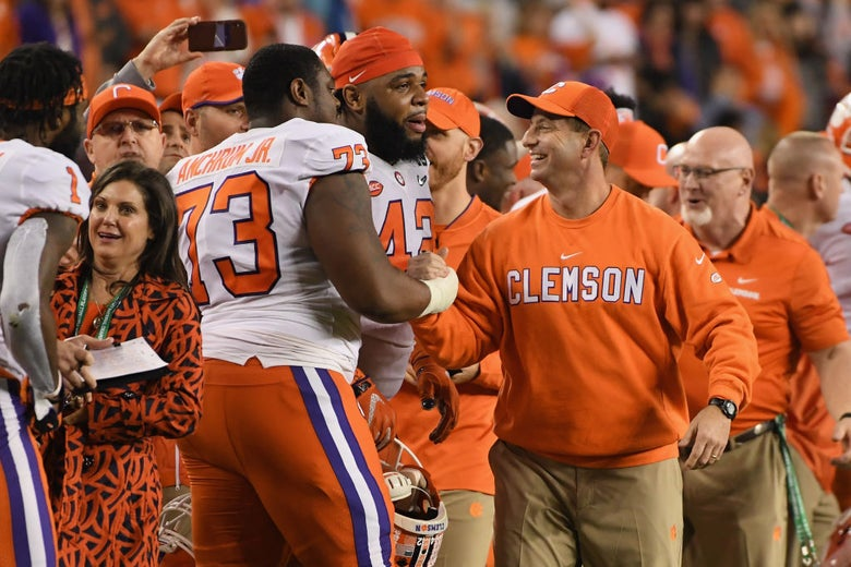 Anchrum shakes a smiling Swinney's hand on the sideline as Wilkins looks on.