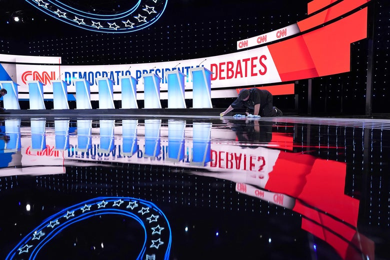 A worker cleans the empty debate stage.