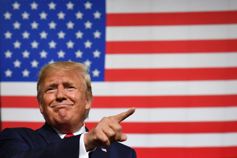 President Donald Trump, pointing, in front of an American flag.