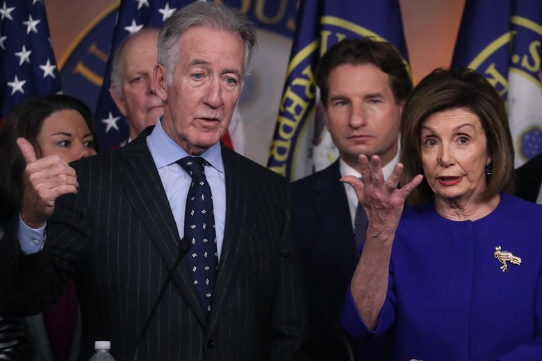 Richard Neal gestures from behind a podium with Nancy Pelosi and other House Democrats beside him.