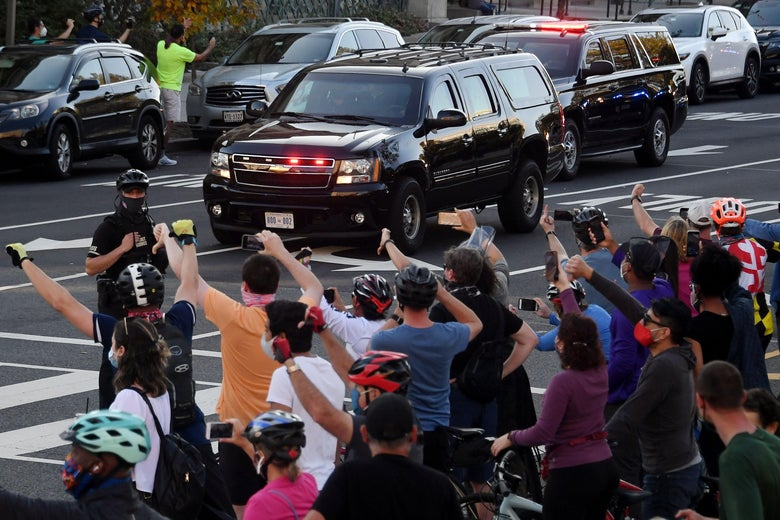 People react as the motorcade carrying President Donald Trump returns to the White House on November 7, 2020 in Washington, D.C.