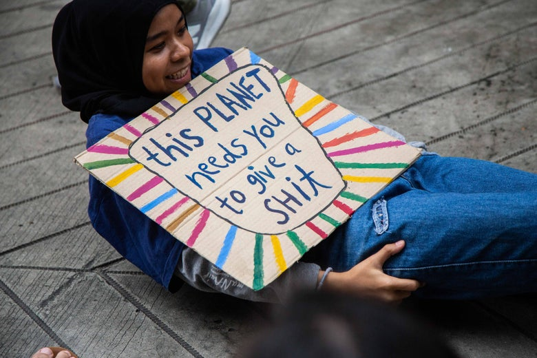 "A girl holds a sign that says ""this planet needs you to give a shit."""