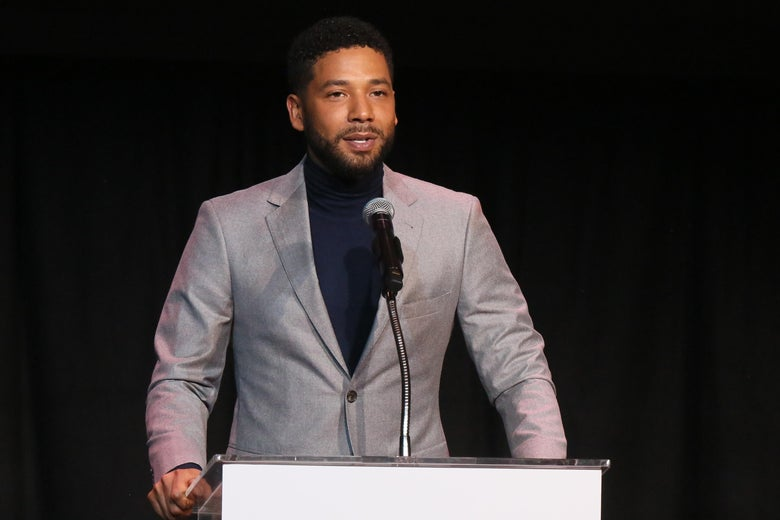 Jussie Smollett standing at a podium, wearing a grey suit.