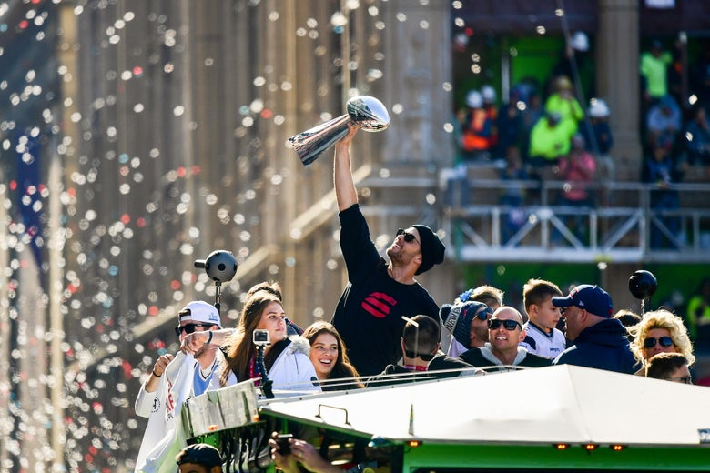 New England Patriots' Tom Brady holds the Vince Lombardi trophy during the Super Bowl victory parade.