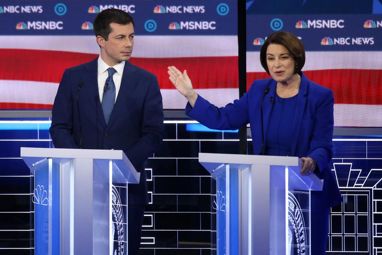 Pete Buttigieg and Amy Klobuchar seen on a debate stage. Klobuchar gestures toward Buttigieg.