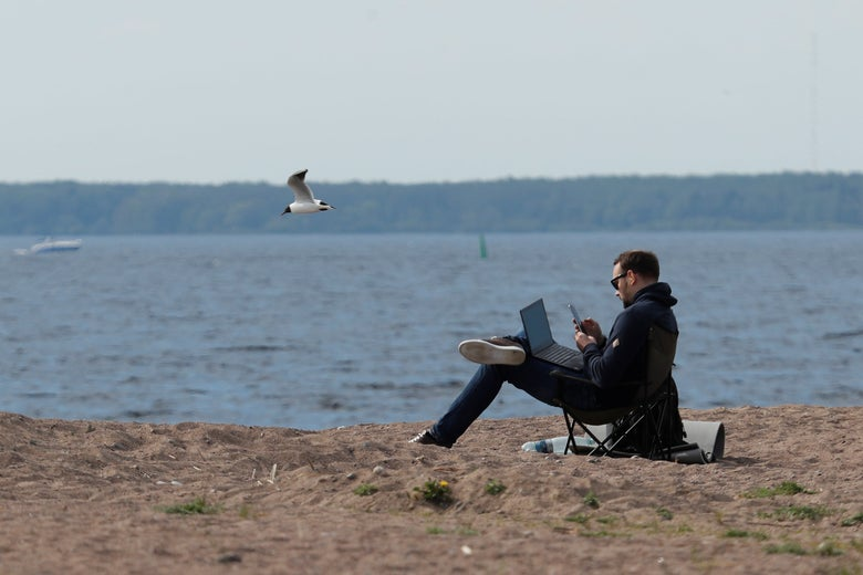 A man uses his smartphone and has a laptop in his lap as he sits in a camping chair on a beach