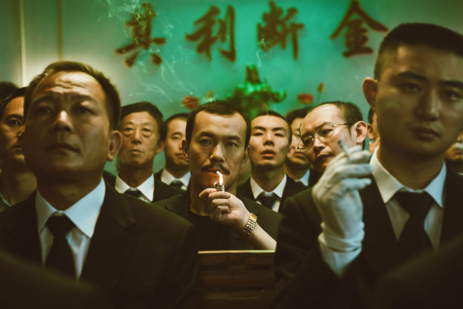 Bin lighting a cigarette in a crowded space in Ash Is Purest White.