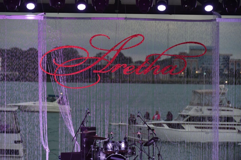 A drum set on an empty stage. In the background, an image of boats on a river, streaked with purple string, and the word Aretha in red script.