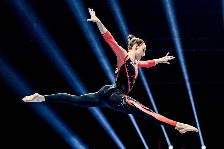 Voss in midair doing a split in her unitard