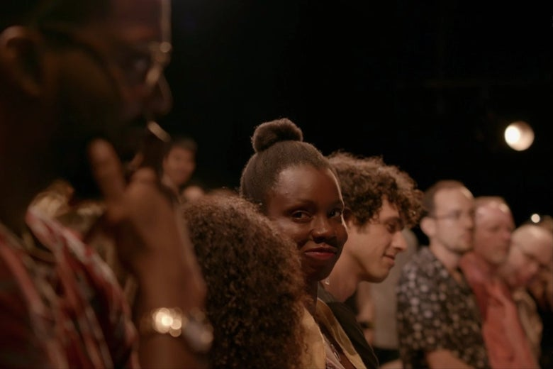 Adepero Oduye, stands in a theater audience, smiling at another person in the foreground.