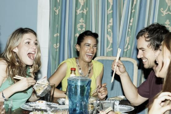 People laugh around a dinner table.