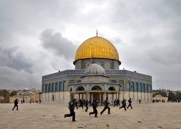 Israeli riot police chase Palestinian stone-throwers (unseen) past the Dome of the Rock mosque following Friday prayers at Jerusalem's al-Aqsa mosque compound, on December 6, 2013.