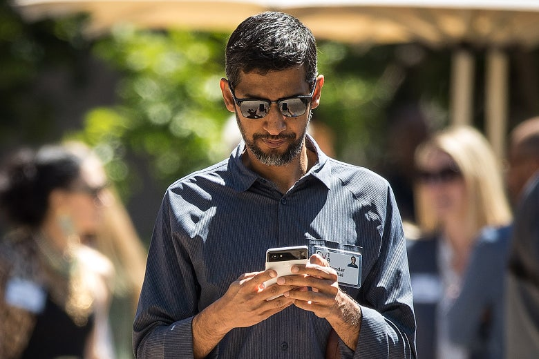 Sundar Pichai, outside, looking down at his smartphone.