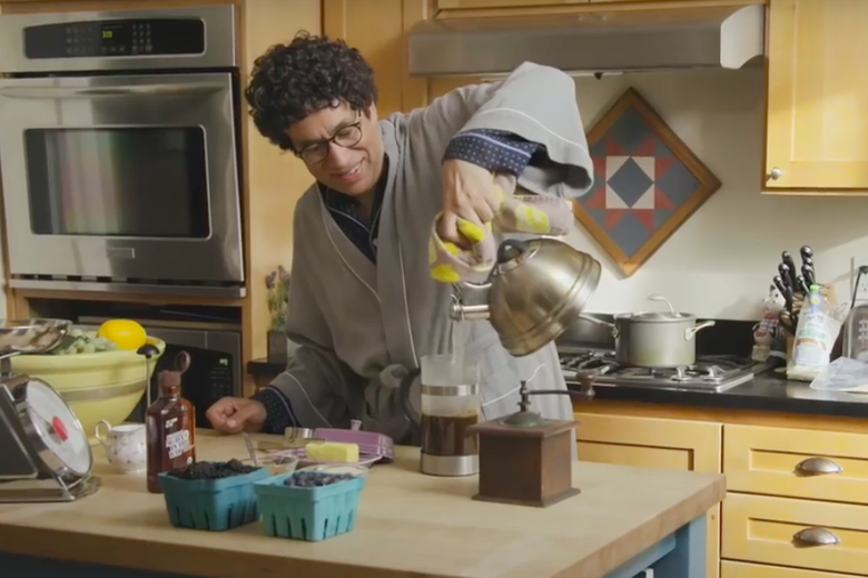 A beaming Fred Armisen, wearing a bathrobe, makes coffee in a rustic kitchen