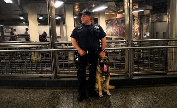 A police officer and his dog, Buster, watch pedestrians in the subway station.