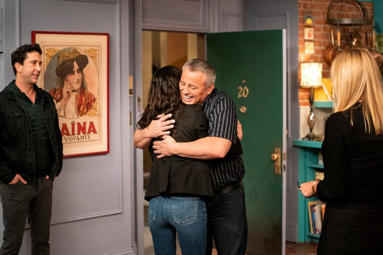 Courteney Cox and Matt Leblanc embrace on the set of friends as Lisa Kudrow and David Schwimmer look on.