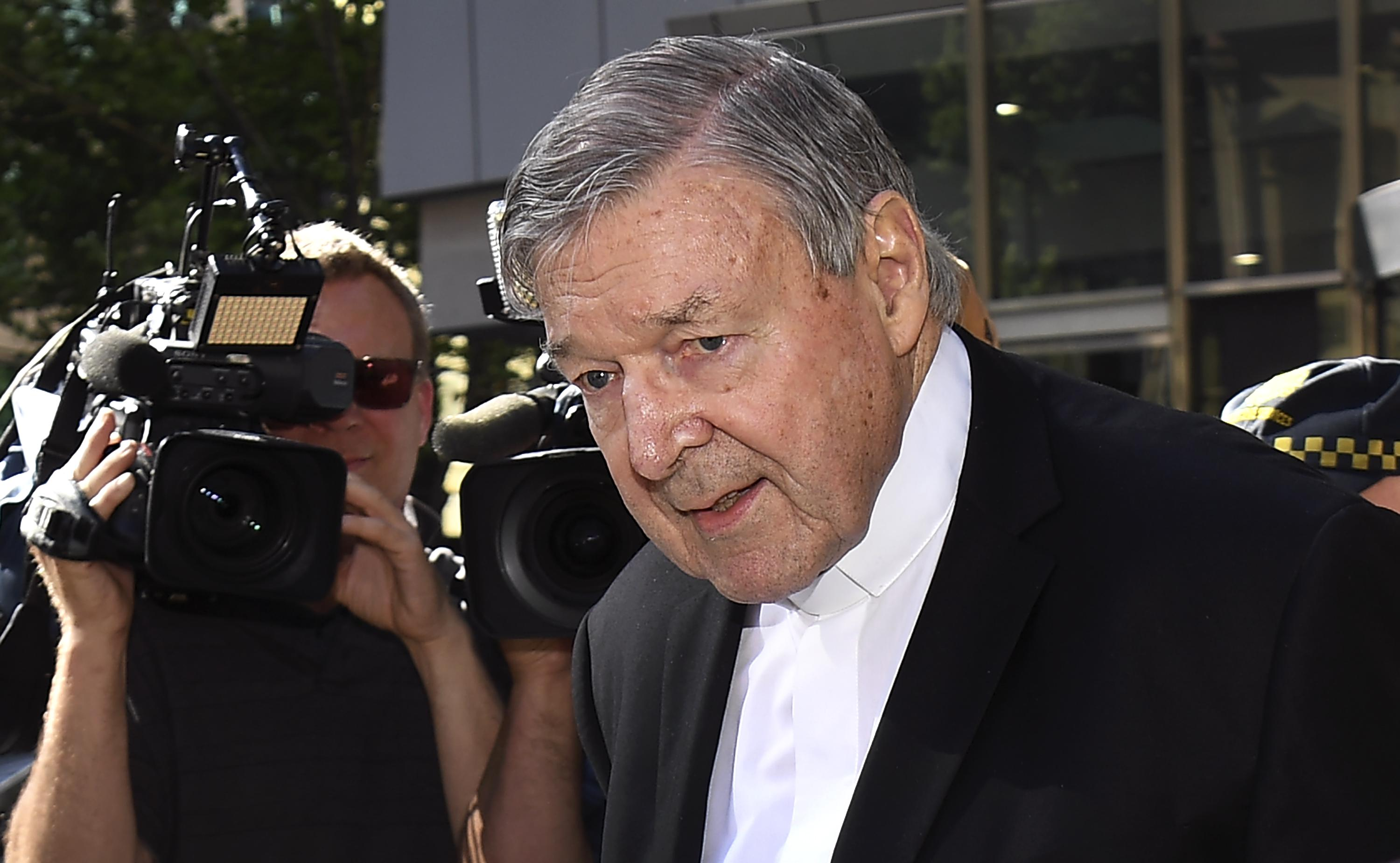 Pell, with his head bent downward, walks through a crowd of reporters. Behind him, a camera is trained on him.