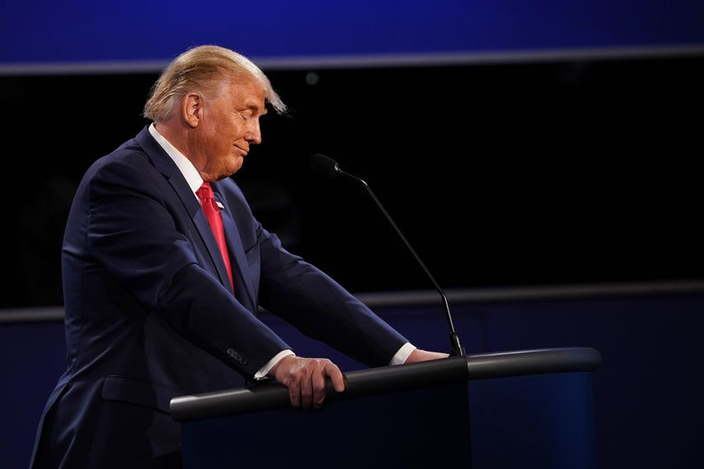 Trump smirks as he stands at his lectern on the debate stage
