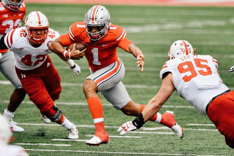 Justin Fields runs through through two other players during a football game.