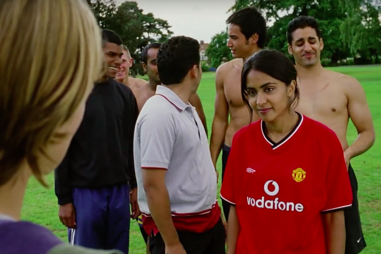 Parminder Nagra, wearing a red jersey, stands on a soccer field in front of a group of men, some of them shirtless.