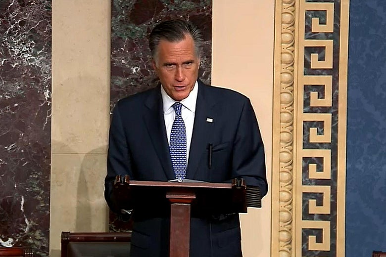Romney speaks at a podium, looking solemn, in the Senate chamber.