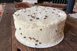 A white, textured cake flecked with chocolate shavings.