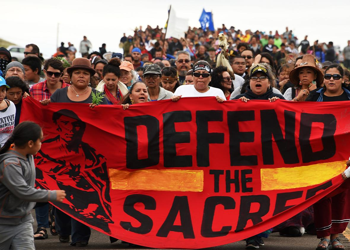 Native Americans march to a burial ground sacred site that was disturbed by bulldozers building the Dakota Access Pipeline, near the encampment where hundreds of people have gathered to join the Standing Rock Sioux Tribe's protest of the oil pipeline that is slated to cross the Missouri River nearby, September 4, 2016 near Cannon Ball, North Dakota.