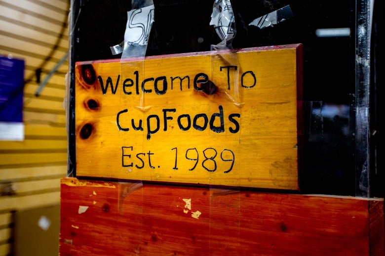 "A piece of wood carved to read, ""Welcome to CupFoods Est. 1989."""