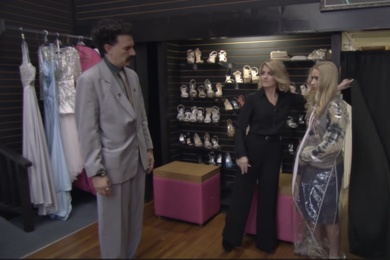 Borat wears his signature grey suit and mustache. His daughter is dressed in a suitbag and barely visible.