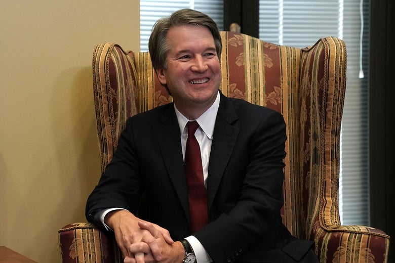 Brett Kavanaugh seated and smiling.