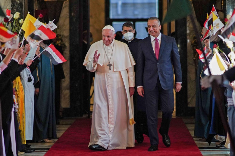 Pope Francis and Iraq's Prime minister walk down an aisle lined with people greeting them with flags.