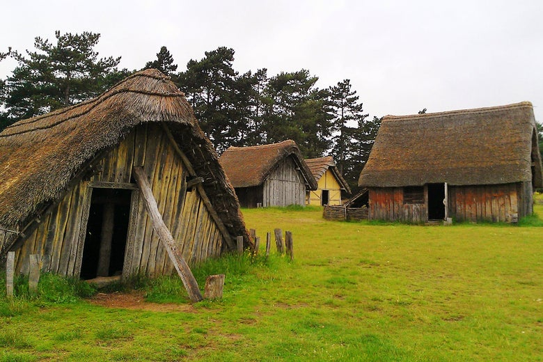 Four dumpy-looking thatched-roof buildings against a gray sky in a wet field.