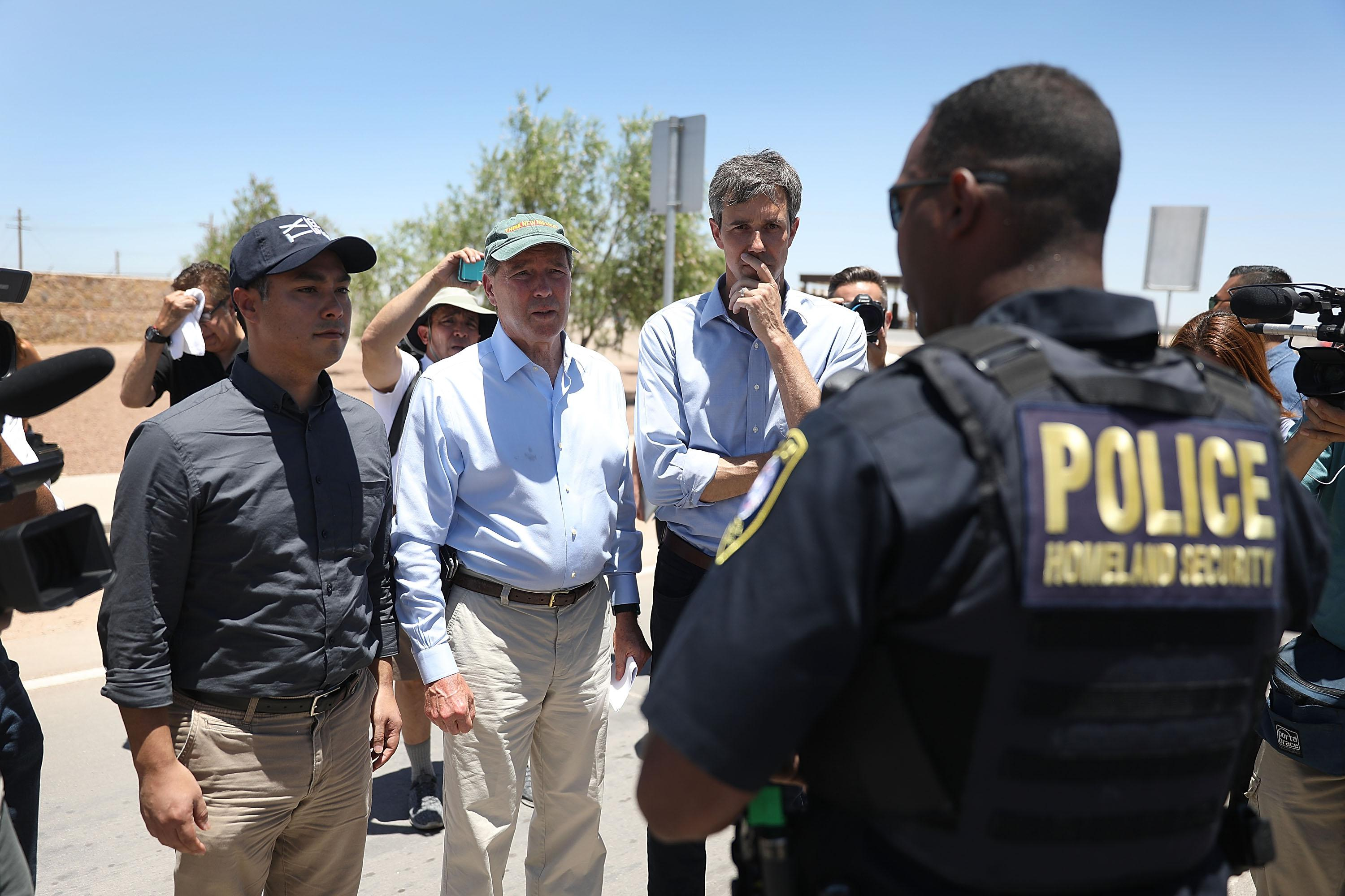 Rep. Joaquin Castro (D-TX), U.S. Senator Tom Udall (D-NM) and Rep. Beto O'Rourke (D-TX)(L-R) are briefed by a Department of Homeland Security police officer before touring a tent encampment near the Tornillo-Guadalupe Port of Entry on June 23, 2018 in Tornillo, Texas.