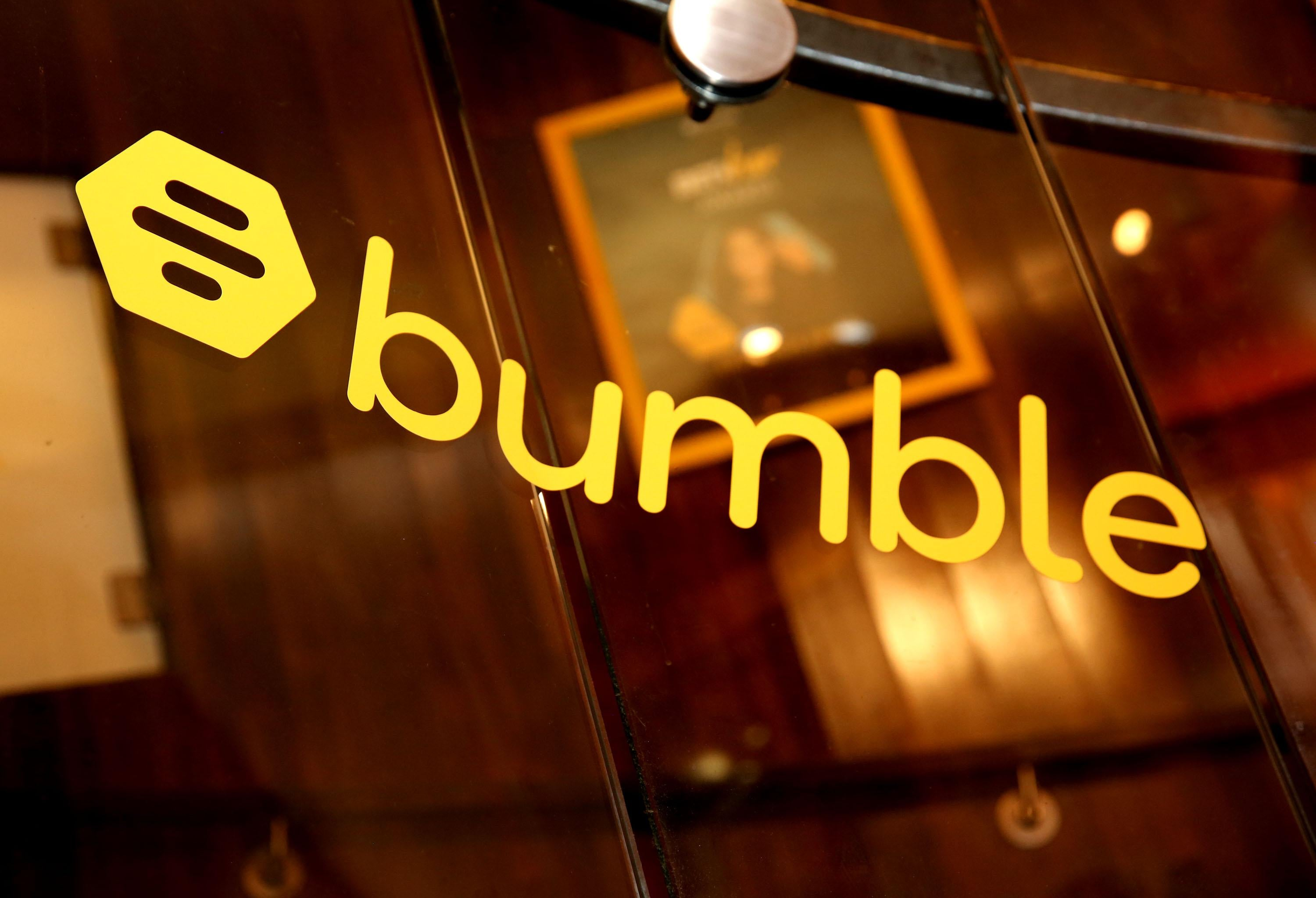 The logo for Bumble, a yellow bee hive, is printed on a glass wall.