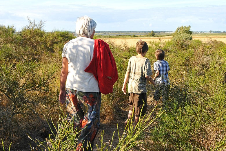 A grandmother keeping her distance while hiking with two grandchildren.