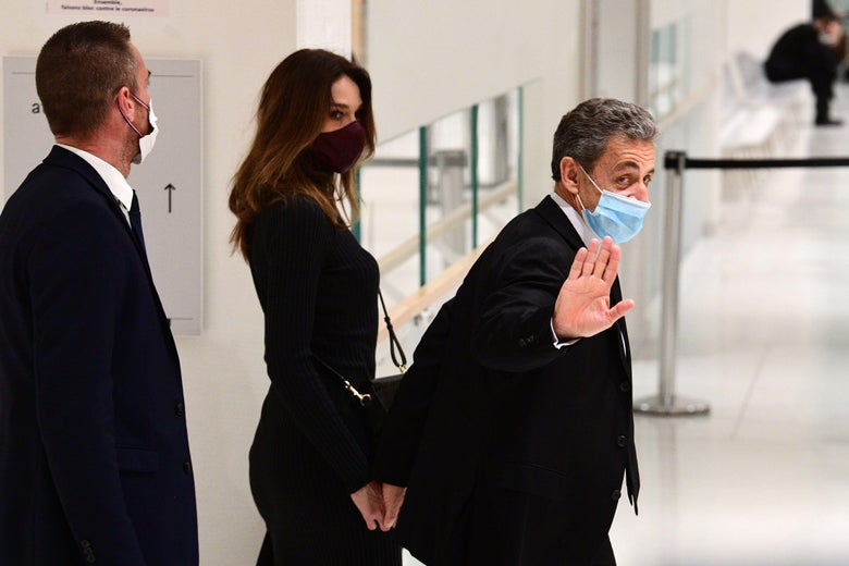 Sarkozy waves to the camera with one hand and holds his wife's hand with the other as they walk through a hallway