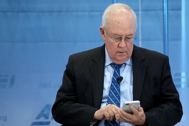Ken Starr looks down at his smartphone while onstage at an event.