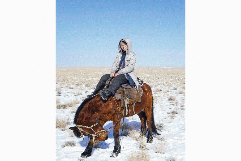 Li Juan on a horse in the snow-covered desert.