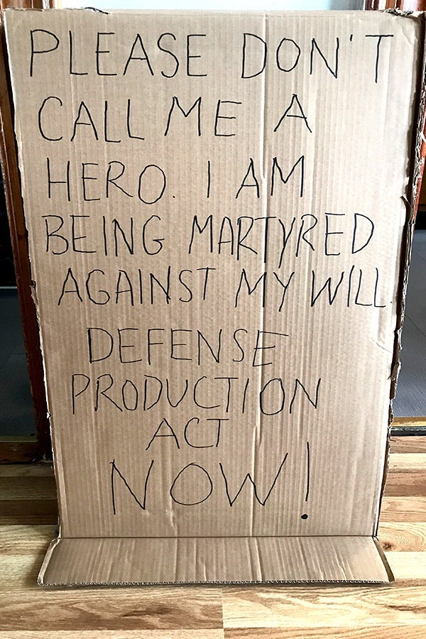 "A cardboard sign that says ""PLEASE DON'T CALL ME A HERO. I AM BEING MARTYRED AGAINST MY WILL. DEFENSE PRODUCTION ACT NOW!"""
