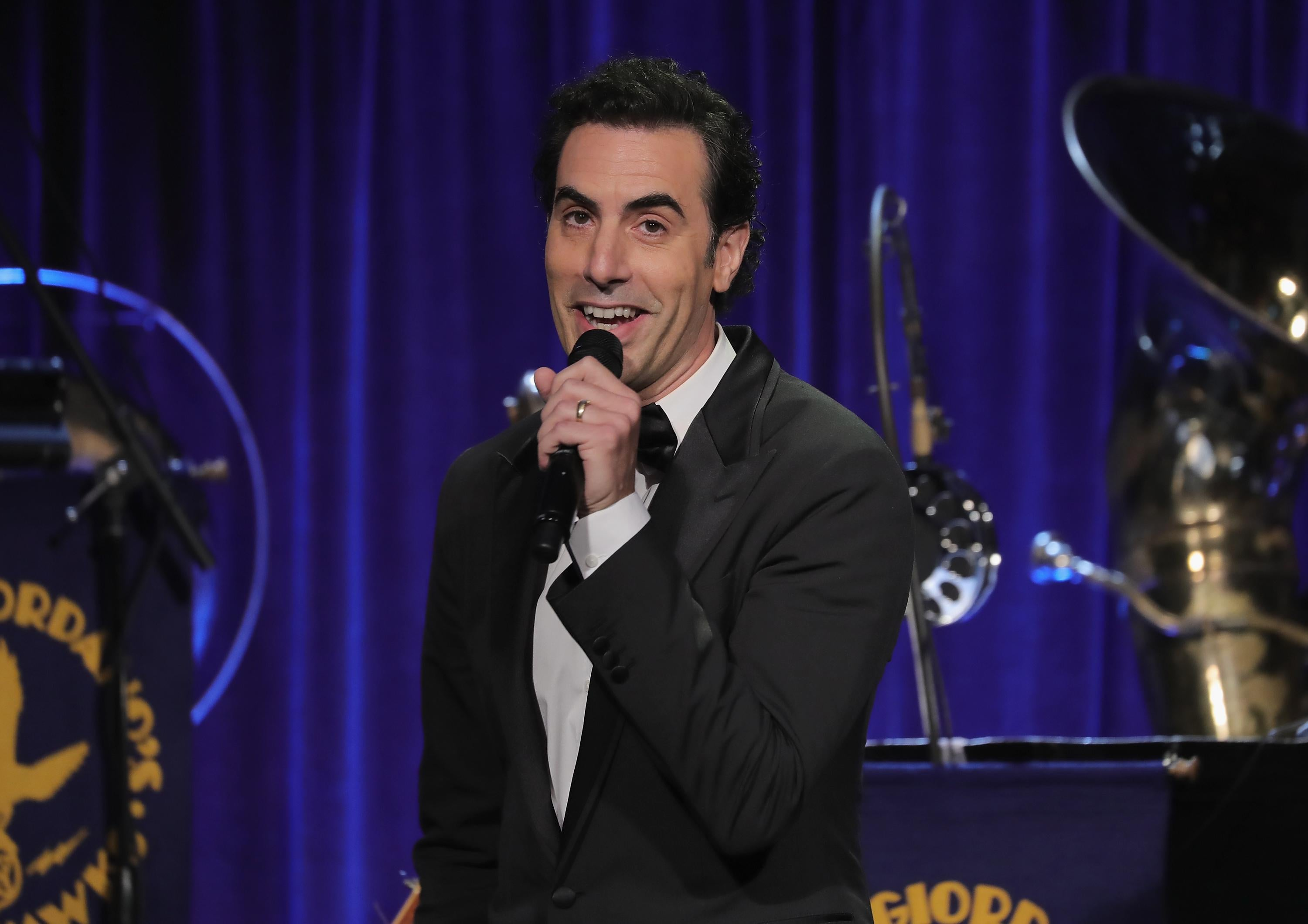Sacha Baron Cohen holds a microphone onstage at the Friars Club in New York City.